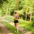 Attractive blonde woman is running in the woods — Stock Photo