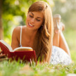 Attractive woman laying on a grass field with a book — Stock fotografie