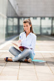 Brunette female student sitting on the floor with notebook — Stock Photo