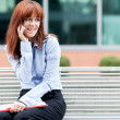 Red hair Businesswoman is sitting on a metal bench and phoning — Stock Photo