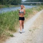 Beautiful blonde woman running along the riverside — Stock Photo #37411111