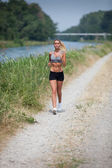 Beautiful blonde woman running along the riverside — Stock Photo