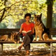 Woman is sitting on a bench with two german shepherds — Stock Photo #38288465