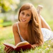 Stock Photo: Attractive woman laying on a grass field with a book
