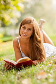 Attractive woman laying on a grass field with a book — Foto Stock