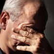 Elderly man with face closed by hand — Stock Photo #12565031