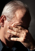 Elderly man with face closed by hand — Stock Photo
