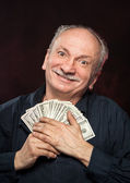 Lucky old man with dollar bills — Stock Photo