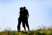 Silhouette of a woman kissing a man — Stock Photo