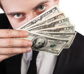 Businessman with a fan of dollars covering the face — Stock Photo