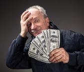 Gubben håller grupp av dollarsedlar — Stockfoto