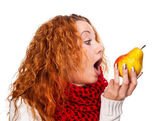 Redheaded girl wants to eat a pear — Stock Photo