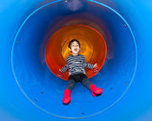 Joyful kid sliding in tube slide — Stock Photo