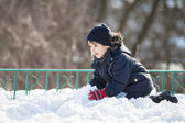 Cute boy playing with snow — Stockfoto