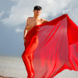 Naked woman on a beach with red fabric — Stockfoto