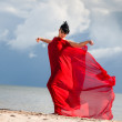 Naked woman on a beach with red fabric — Stock fotografie