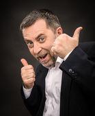 Successful man shows ok sigh on dark background — Stock Photo