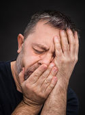Headache. Man with face closed by hand — Stock Photo