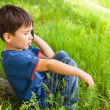 Boy in green grass talking on cell phone — Стоковая фотография