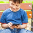 Boy playing games on smartphone — Stockfoto