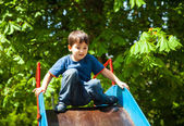 Cute boy playing on slide — Stock Photo