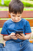Boy playing games on smartphone — Stock Photo
