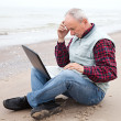 Old man with notebook on beach — Lizenzfreies Foto