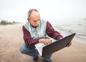 Old man with notebook on beach — Stock Photo