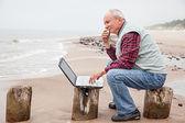 Alter mann mit notebook am strand — Stockfoto