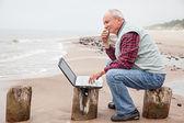 Oude man met laptop op strand — Stockfoto