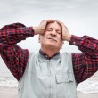 Elderly man suffering from a headache on sea background — Stock Photo