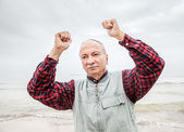 Older man with hands up at the coast — Stock Photo
