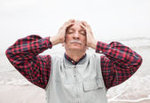 Elderly man suffering from a headache on sea background — Stock Photo