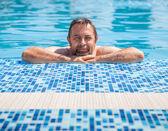 Man van middelbare leeftijd in een zwembad — Stockfoto
