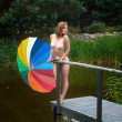 Naked girl with umbrella near small pond — Stock fotografie