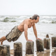 Stock Photo: Mdoing pushups on beach