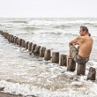 Stock Photo: Middle-aged msitting near sea