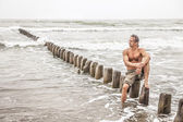 Middle-aged man sitting near the sea — Foto Stock