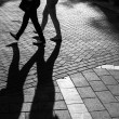 Foto Stock: Shadows of people walking street