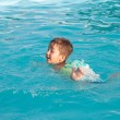 Stock Photo: Little boy learning to swim in the pool