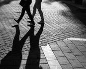 Shadows of people walking street — Stockfoto