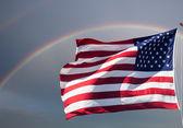 American flag against a cloudy sky with a rainbow — Stock Photo