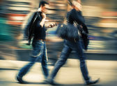 Man and woman talking on a cell phone in a hurry — Foto de Stock