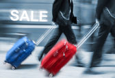 Sale. People with suitcases in a hurry. — Stock Photo