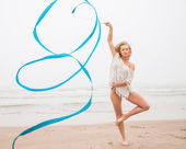 Gymnast vrouw dans met lint op het strand — Stockfoto