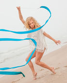 Gymnast woman dance with ribbon on the beach — Stock Photo