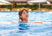 Young woman relaxing in a swimming pool — Stock Photo