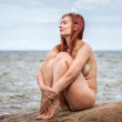 Nude woman sitting on stone — Stock fotografie