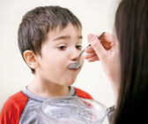 Little boy is being fed using spoon — 图库照片