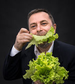 Man holding and eating lettuce — Stock Photo